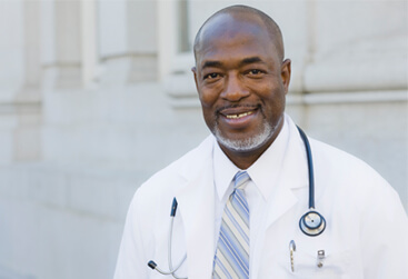 mature doctor standing in front of hospital